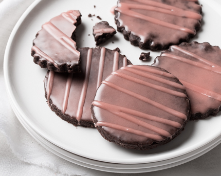 Chocolate cookies with a dark pink glaze on a plate