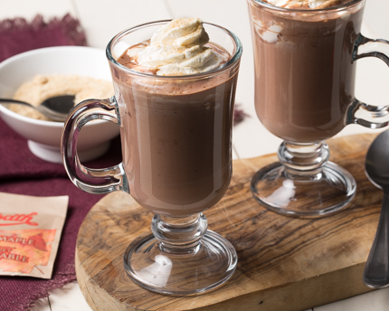 Two glass mugs of hot chocolate with whipped cream on top