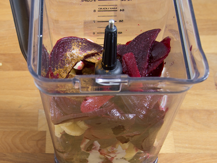 Slices of beet, cherries, apples, and bananas in a blender