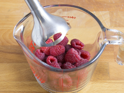 A measuring cup full of raspberries about to be pureed