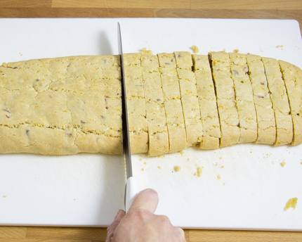 Slicing a loaf of biscotti on a cutting board with a serrated knife