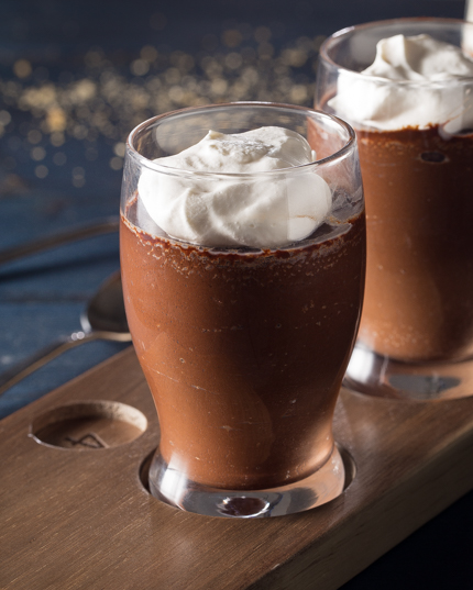 Two chocolate pots de crème with whipped cream in beer glasses on a tasting flight board