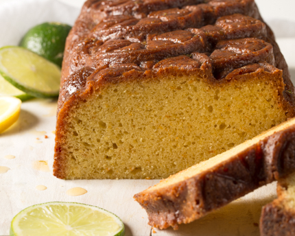 A loaf of pound cake sliced at one end, on a plate with sliced lemons and limes
