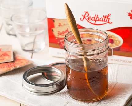 A mason jar of maple simple syrup in front of a box of Redpath sugar