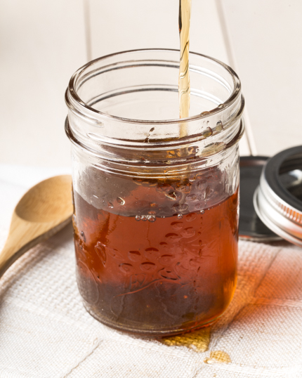 A mason jar with maple simple syrup pouring in