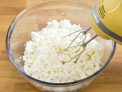 Cottage cheese and cream cheese in a mixing bowl, with a hand mixer