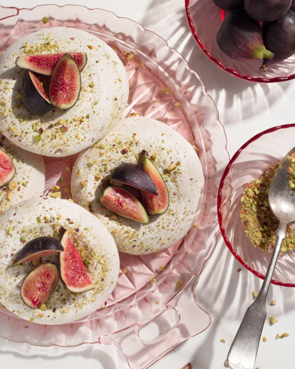 Meringues on a glass dish, topped with pistachio and figs