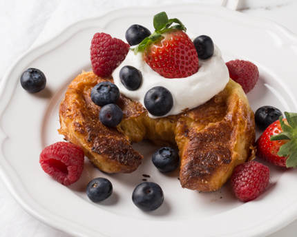 A baked croissant topped with whipped cream and berries