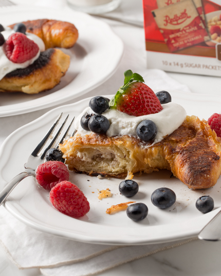 A baked croissant topped with whipped cream and berries with a bite missing, and Redpath® Brown & Maple Sugars box in the background