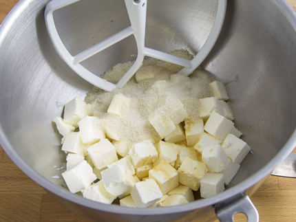 Cubes of cream cheese and sugar in a stand mixer bowl