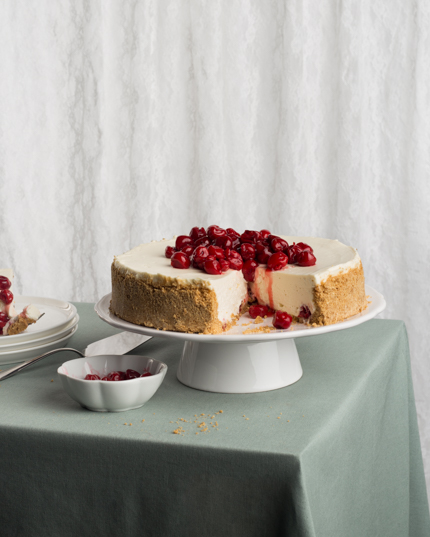 A cherry cheesecake with a slice missing on cake stand on a table