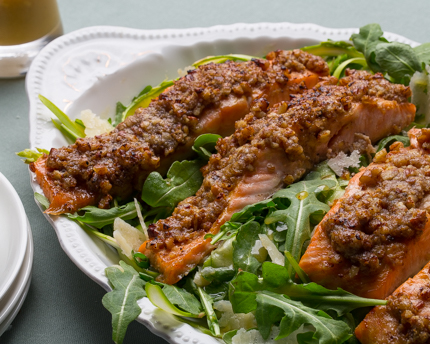 Arugula salad with crusted salmon fillets in a white bowl