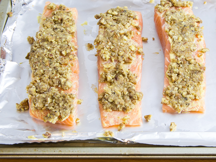 Uncooked, nut-crusted salmon fillets on a foil lined baking tray