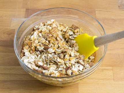 Oats, pecans, and coconut being mixed in a bowl with butter, honey, and juice