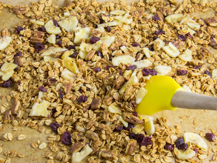 Stirring bananas and cranberries into granola on a parchment-lined baking sheet