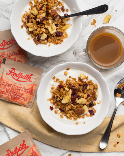 Two bowls of yogurt topped with banana and pecan granola with a mug of coffee and packets of Redpath Brown & Maple Sugars
