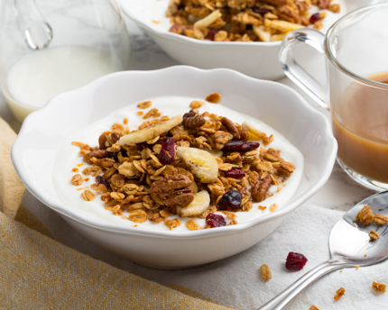 A bowl of yogurt topped with banana and pecan granola