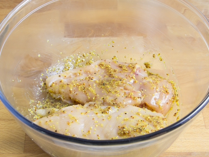 Raw chicken breasts in a glass bowl, coated with seasoning