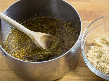 Cooking pot full of thyme, water, and elderflowers, with a wooden stirring spoon