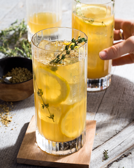 Two glasses of lemonade on ice with lemon slices and garnished with thyme