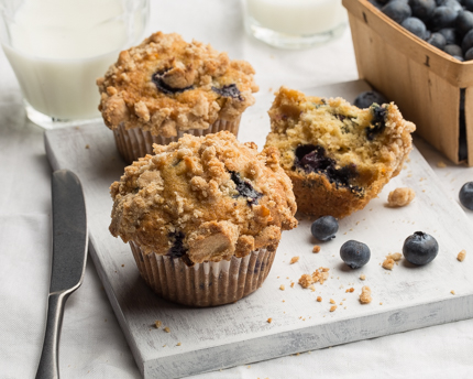 Three blueberry muffins served with milk and a basket of blueberries