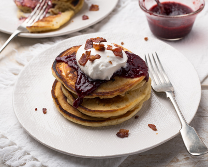A plate of pancakes with berry topping, whipped cream, and crumbled bacon