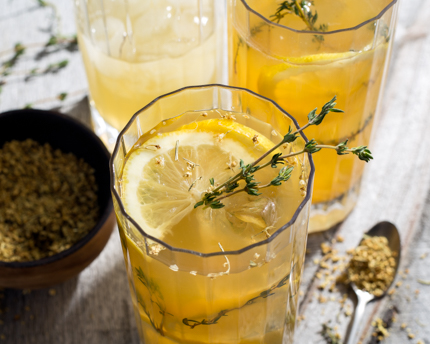 Top view of a glass of lemonade garnished with thyme