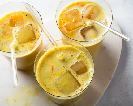3 glasses of turmeric latte on ice with straws