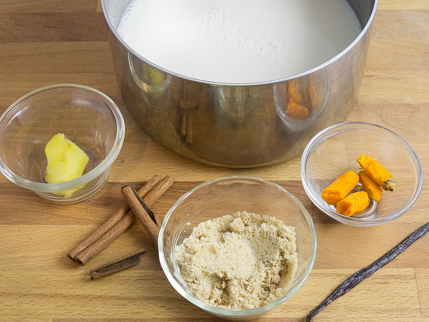 A pot of milk surrounded by cinnamon, vanilla, ginger, golden yellow sugar, and turmeric
