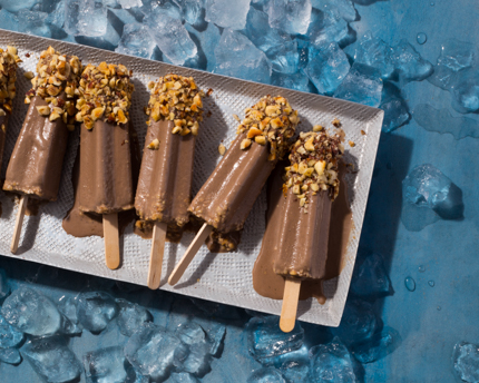 Chocolate Kulfi pops with crushed hazelnuts melting on a tray