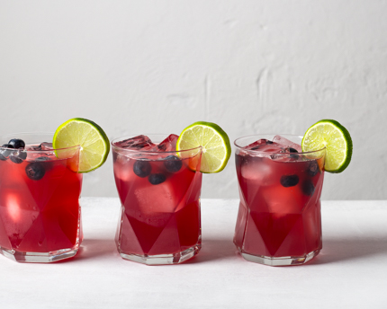 Three glasses of Blueberry Beer Cocktail garnished with blueberries and lime