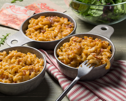 Three bowls of macaroni and cheese, with a salad and Redpath Brown & Maple Sugars