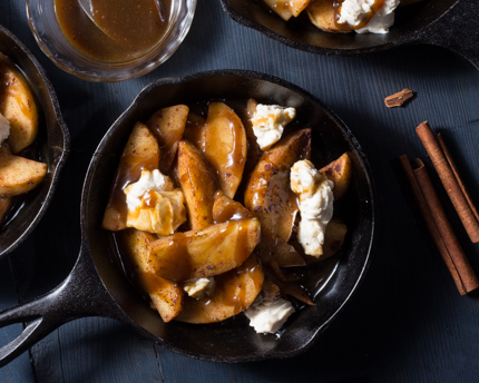 A cast iron skillet of dessert poutine including sliced apples, caramel sauce and sweetened cream cheese