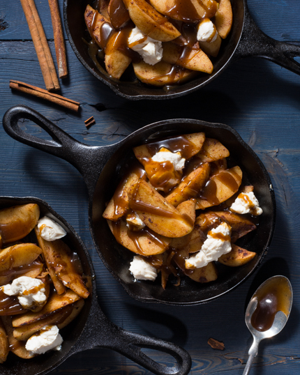 Three cast iron skillets of dessert poutine including sliced apples, caramel sauce and sweetened cream cheese