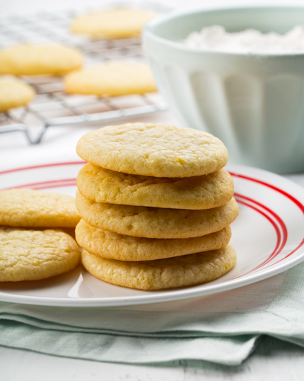 Lemon sugar cookies stacked on plate with more cookies cooling in the background