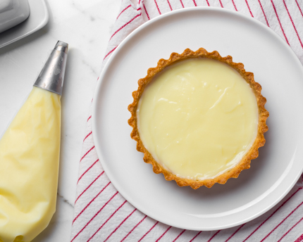 A piping bag beside a tart filled with cream