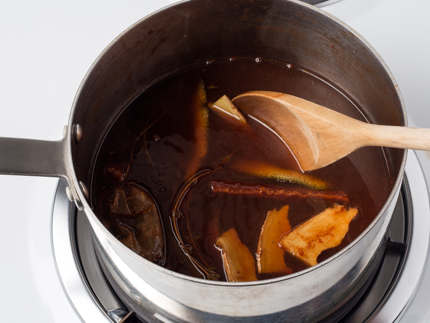 Stirring fruit juice and seasonings in a pot with a wooden spoon