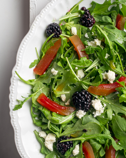 Pickled watermelon rinds and blackberries on a salad with goat cheese