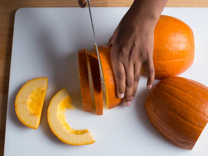Slicing a pumpkin with a large knife