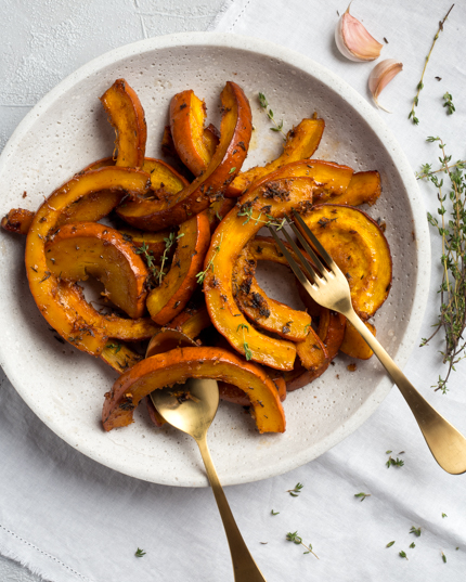 Roasted pumpkin sections in a dish with seasoning and a fork and spoon