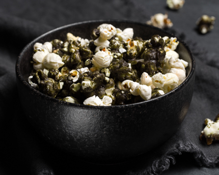 Black matcha caramel corn in a black bowl