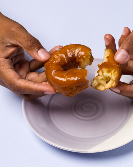 A woman's hands breaking a piece off an old-fashioned doughnut with glaze