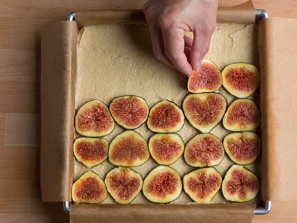 Placing fig slices on unbaked dessert in a baking pan