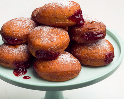 A stack of sufganiyot dripping jelly on a cake stand