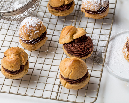 Choux pastry puffs filled with chocolate ganache on a wire cooling rack