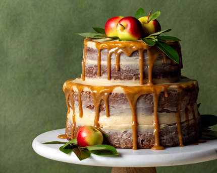 Tiered apple spice naked cake on a cake tray with apples and a green backdrop