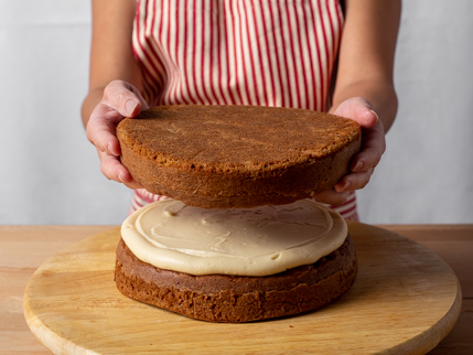 Placing the top layer on a round layer cake