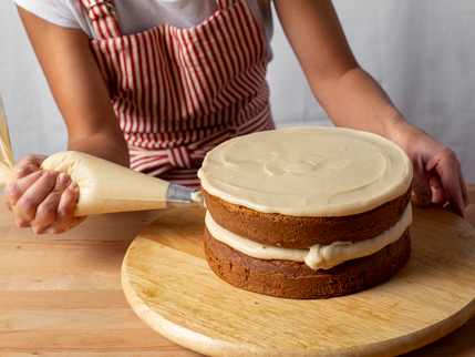 Piping frosting on the side of a layer cake