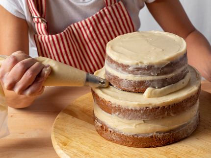 Piping icing between the levels of a tiered layer cake