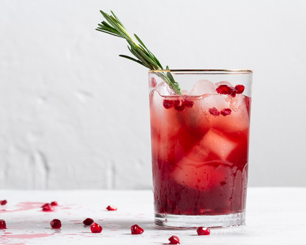 A glass of pomegranate and cranberry cocktail garnished with rosemary